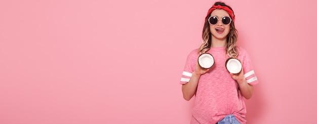 Belle Jeune Fille En T-shirt Rose Et Lunettes Tenant Des Noix De Coco Sexy Drôles Sur Fond Rose Photo gratuit