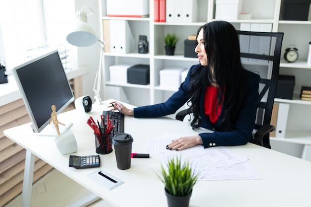 Belle jeune fille travaillant avec un ordinateur et des documents au bureau à la table Photo Premium