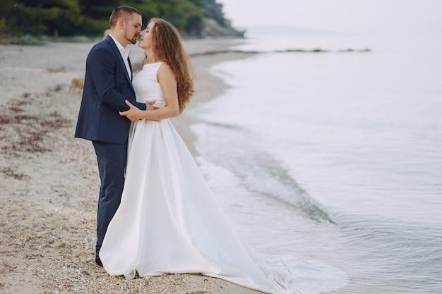 Belle jeune mariée aux cheveux longs en robe blanche avec son jeune mari sur la plage Photo gratuit