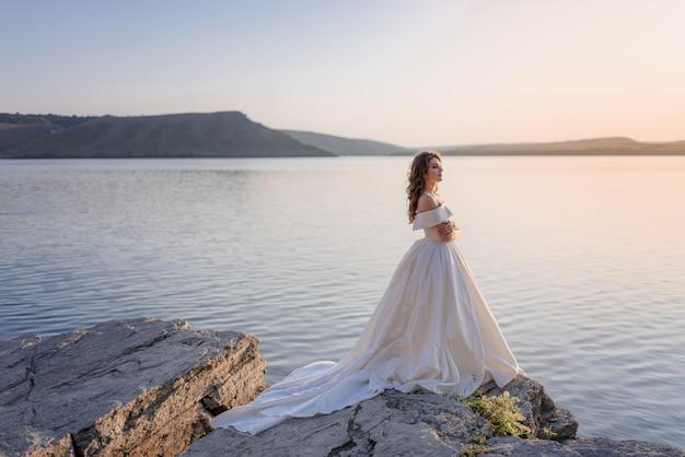 Belle Jeune Mariée Caucasienne Se Tient Au Bord D'une Falaise Près De La Mer Photo gratuit