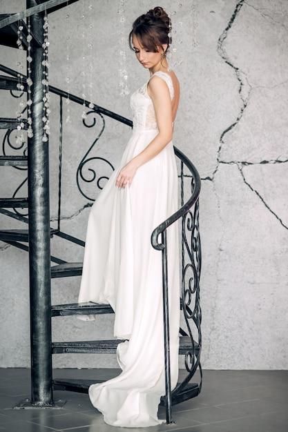 Belle Jeune Mariée Debout Sur Un Escalier Forgé Dans Un Intérieur Lumineux Photo Premium