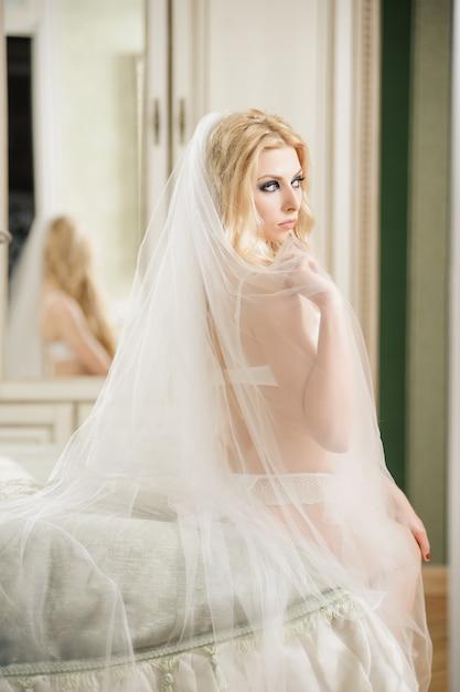 Belle jeune mariée porte de la lingerie blanche et voile, belle femme est assise sur le lit dans sa chambre Photo Premium