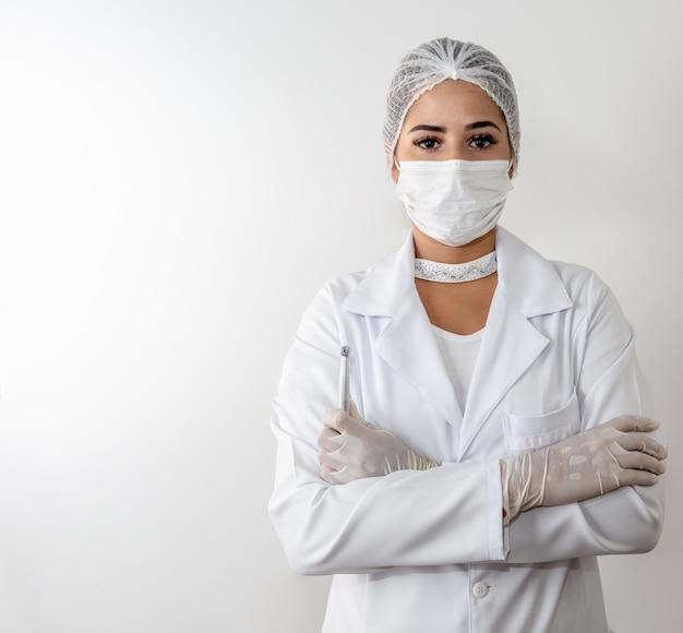 Belle jeune médecin femme en blouse blanche médicale et un masque de protection et une seringue. Photo Premium