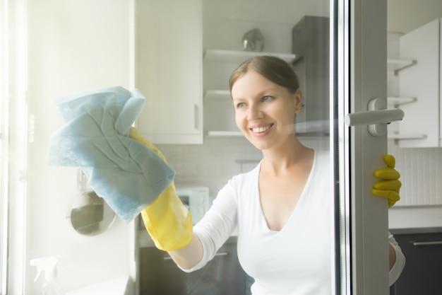 Belle jeune ménagère souriante qui lave les fenêtres Photo gratuit