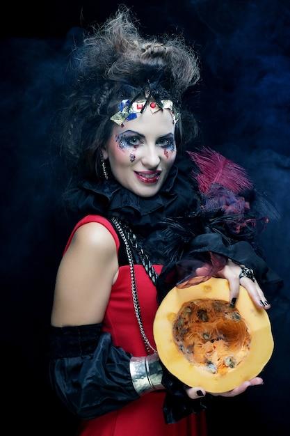 Belle Jeune Sorcière Avec Malke Lumineux Tenant Une Citrouille Sur Fond Sombre Photo Premium