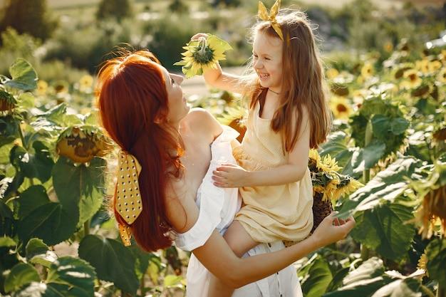 Belle et jolie famille dans un champ avec des tournesols Photo gratuit