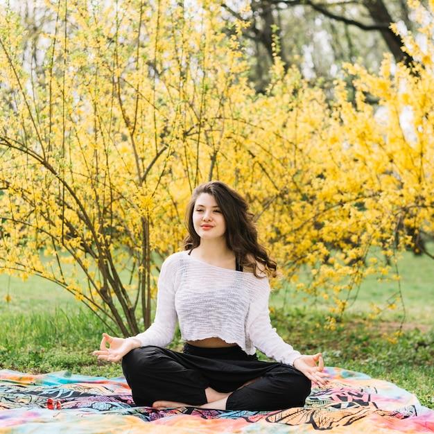 Belle jolie femme faire du yoga dans le parc Photo gratuit