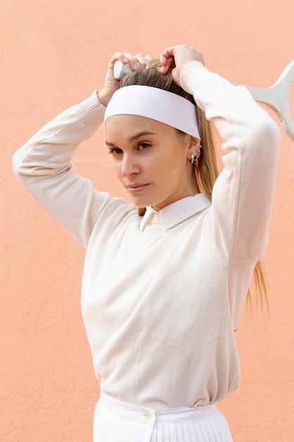 Belle joueuse de tennis attrape la queue de cheveux Photo gratuit