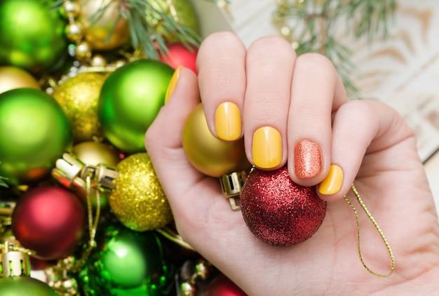 Belle main féminine avec la conception des ongles jaune. manucure de noël. Photo Premium