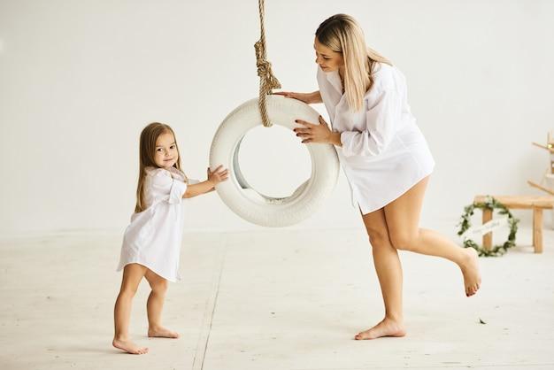 Une belle maman enceinte joue avec sa fille sur une balançoire dans une pièce blanche Photo Premium