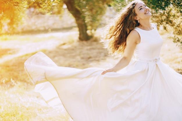 Belle mariée aux cheveux longs dans une magnifique robe blanche marchant dans la nature Photo gratuit
