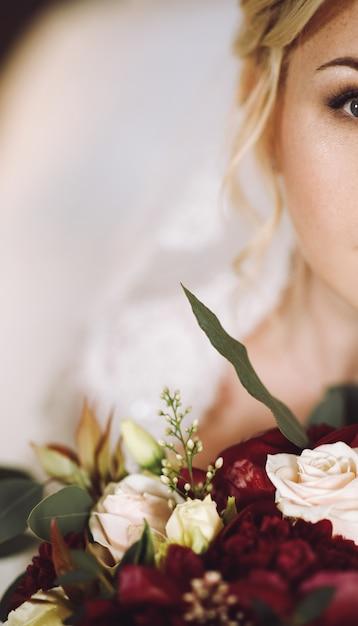 Belle mariée blonde regarde par-dessus le bouquet de mariage rouge foncé Photo gratuit