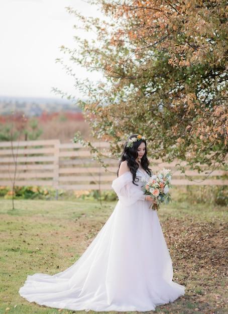 Belle Mariée Caucasienne Avec Bouquet De Mariée Est Debout Sur L'herbe Sèche Près De L'arbre Sur La Chaude Journée D'automne Photo gratuit