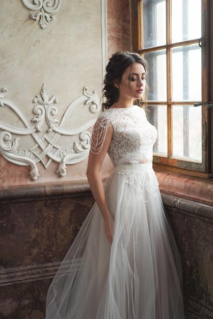 Belle mariée dans le château intérieur de luxe baroque. portrait Photo Premium