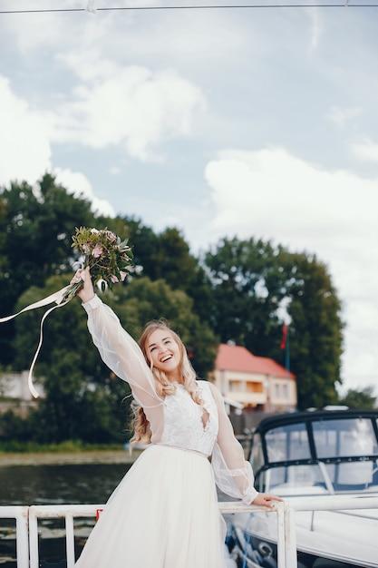Belle mariée dans une longue robe de mariée blanche Photo gratuit
