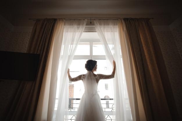 Belle Mariée Dans Une Robe De Mariée Blanche Ouvre Les Rideaux Photo Premium