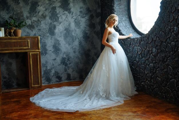 Une belle mariée dans une très belle robe longue avec un train se tient près de la fenêtre. Photo Premium