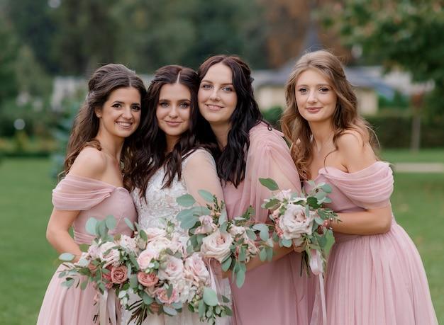 Belle Mariée Avec Des Demoiselles D'honneur Vêtues De Robes Roses Tiennent Des Bouquets Roses Pâles Faits De Roses à L'extérieur Photo gratuit