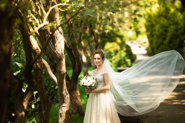 Belle mariée marche dans le parc. le voile de mariage se disperse du vent. portrait de beauté d'une mariée autour d'une nature étonnante Photo Premium