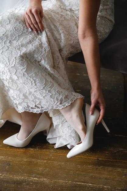 Belle mariée porte des chaussures de mariage. fermer. le jour du mariage ou le matin Photo Premium