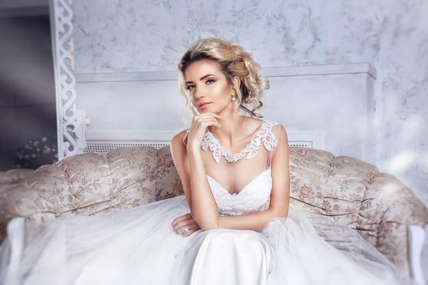 Belle Mariée Posant En Robe De Mariée Assise Sur Un Canapé Dans Un Blanc. Photo Premium