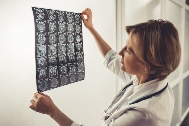Belle médecin en blouse blanche examine les images de rayons x. Photo Premium