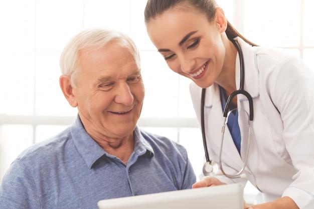 Belle médecin consulte son beau vieux patient Photo Premium