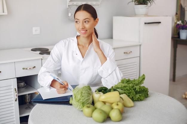 Belle médecin dans une cuisine avec des légumes Photo gratuit