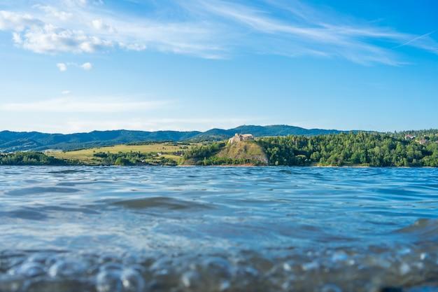Belle Mer Entourée De Collines Herbeuses Sous Le Ciel Nuageux Photo gratuit