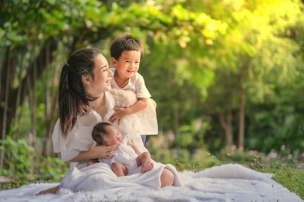 Belle mère et bébé famille dans un parc asiatique Photo Premium