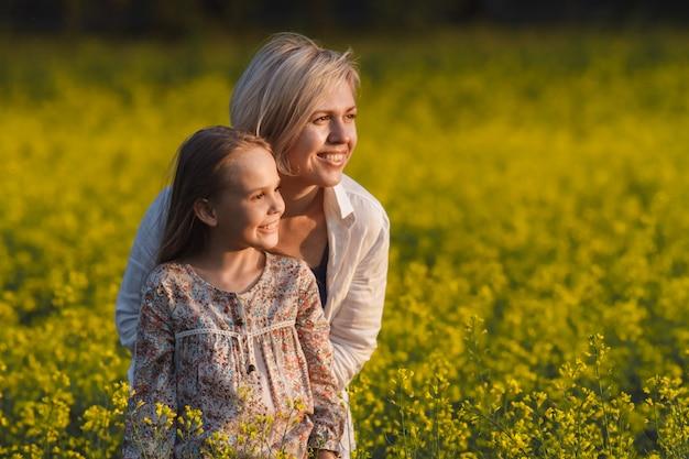 Belle mère et fille sur un champ de colza jaune Photo Premium