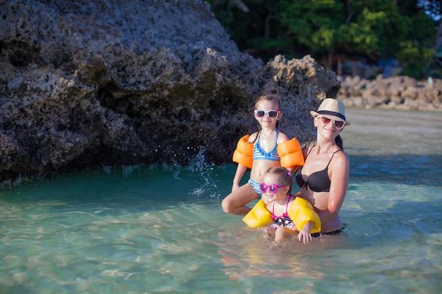 Belle mère et ses deux enfants à la plage exotique sur une journée ensoleillée Photo Premium