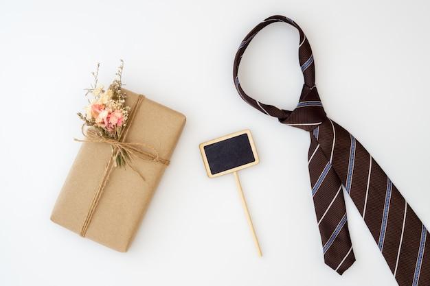 Belle petite boîte-cadeau faite main avec des fleurs et une cravate Photo Premium