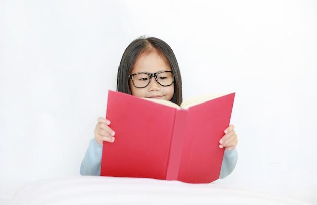 Belle petite fille asiatique enfant heureux lire un livre à couverture rigide allongé sur le lit sur fond blanc. Photo Premium