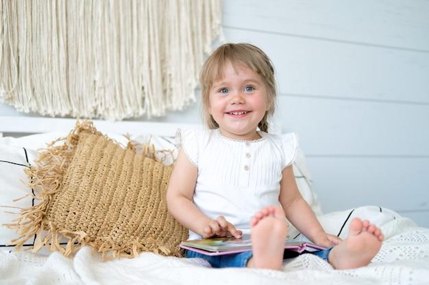 Belle petite fille assise sur le lit et lisant un livre Photo Premium