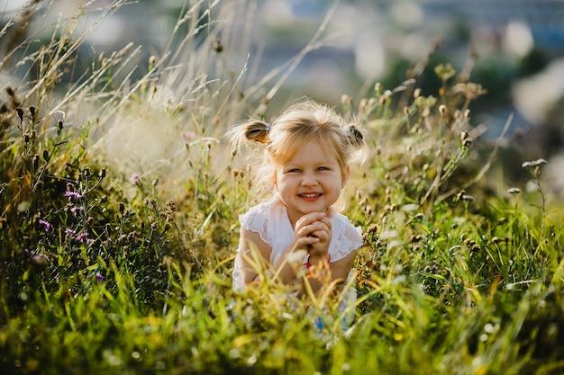 Belle petite fille en chemise blanche et jeans est assis sur la pelouse avec un grand paysage Photo gratuit