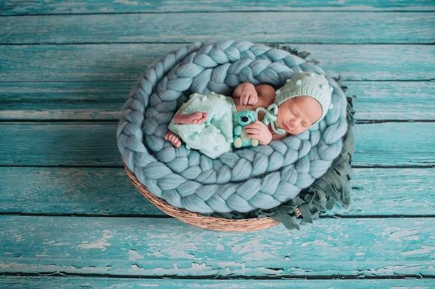 Belle petite fille dort avec un ours bleu sur une couverture bleue dans le panier Photo gratuit