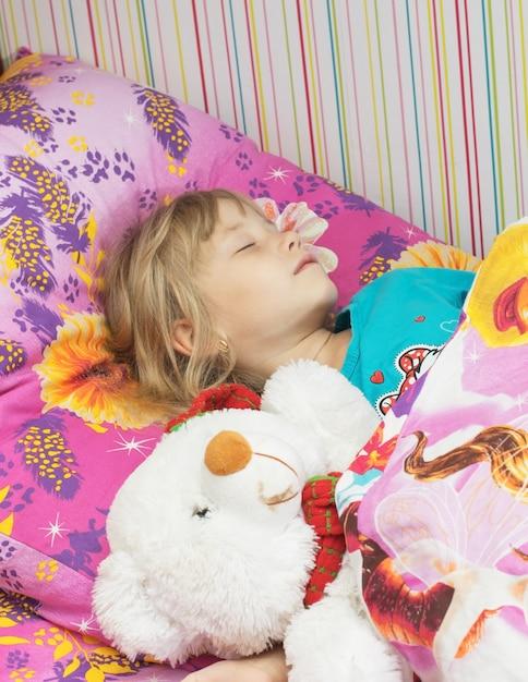 Belle petite fille avec un ours polaire de jouet. Photo Premium