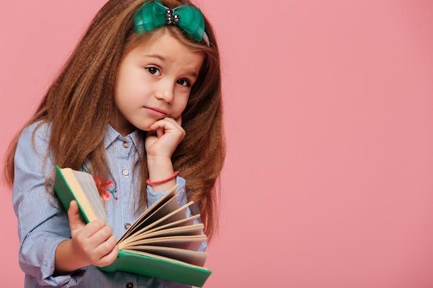 Belle Petite Fille Réfléchie Avec De Longs Cheveux Bruns Soutenant Sa Tête Avec La Main Tout En Lisant Un Livre Ou En Apprenant Des Informations Photo gratuit