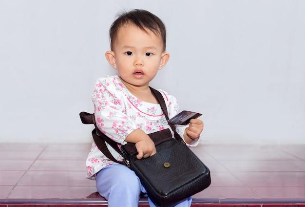 Belle petite fille avec sac détenant une carte de crédit pour faire du shopping sur fond blanc Photo Premium