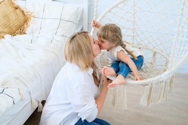 Belle petite fille se balançant dans un fauteuil suspendu dans la chambre à coucher avec sa mère bébé embrasse maman Photo Premium