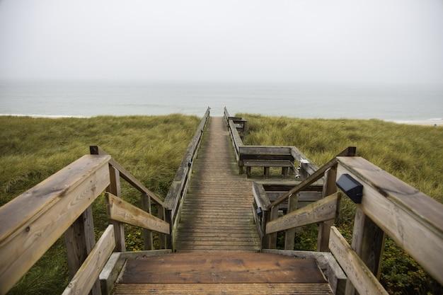 Belle Photo D'un Chemin En Bois Dans Les Collines Au Bord De L'océan à Sylt Island En Allemagne Photo gratuit