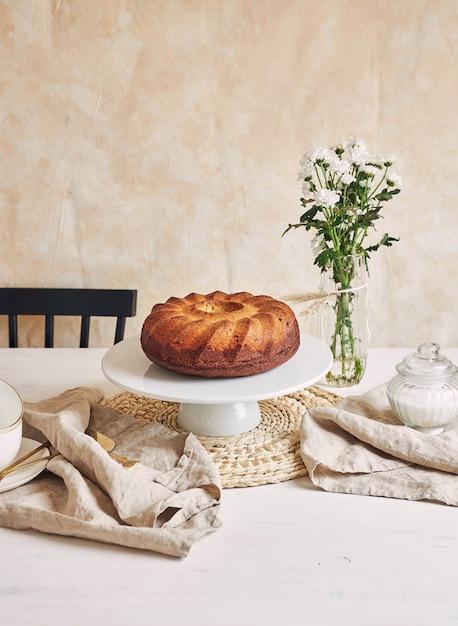 Belle Photo D'un Délicieux Gâteau à L'anneau Posé Sur Une Assiette Blanche Et Une Fleur Blanche à Proximité Photo gratuit