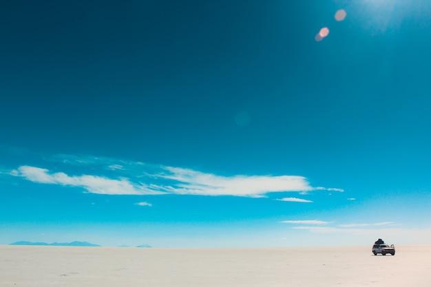 Belle Photo Du Ciel Avec Des Nuages Fanés Par Une Journée Ensoleillée Avec Une Voiture Dans Le Désert Photo gratuit