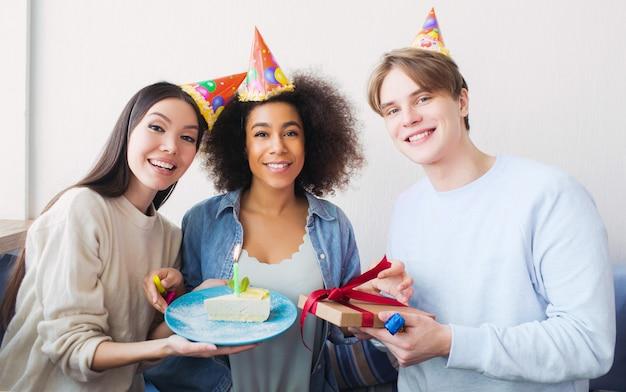 Belle Photo D'une Fille D'anniversaire Et De Ses Amis. Fille Asiatique A Un Morceau De Gâteau. Le Gars Tient Un Cadeau Dans Ses Mains. Tous Sont Heureux. Photo Premium