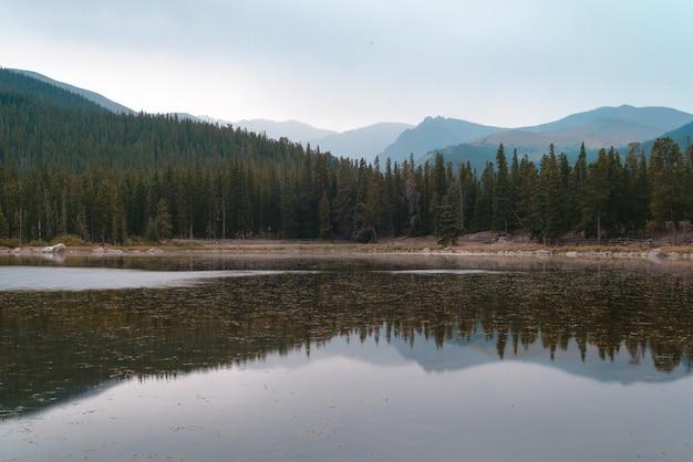 Belle Photo D'un Lac Reflétant Les Arbres Sur La Rive Sous Un Ciel Bleu Photo gratuit