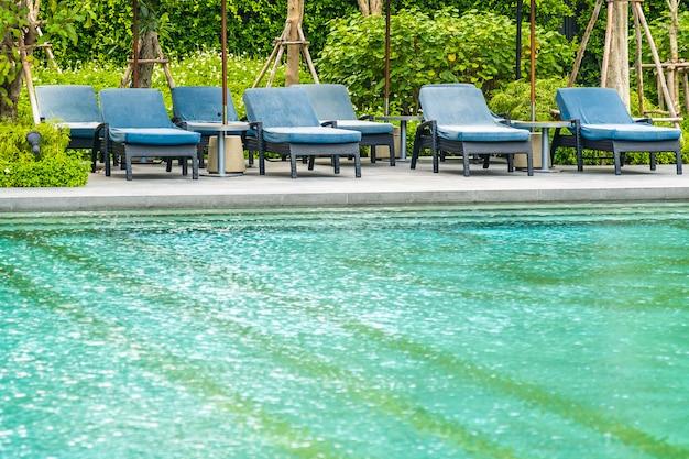 Belle piscine extérieure dans l'hôtel et la station avec chaise et terrasse pour des vacances de loisirs Photo gratuit