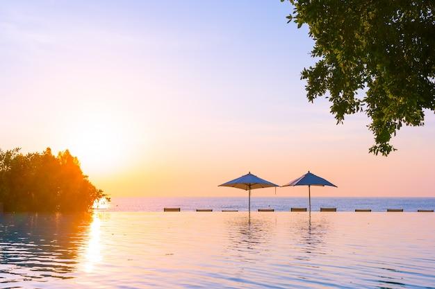 Belle piscine en plein air avec parasol et chaise longue dans le complexe hôtelier pour se détendre Photo gratuit