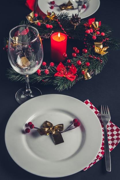 Belle place de dîner de noël pour deux. table décorée d'une guirlande et d'une bougie. Photo Premium