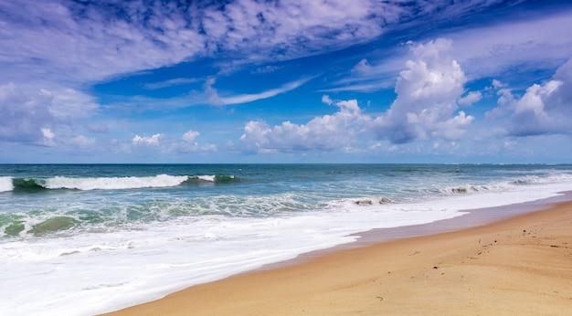 Belle plage de sable tropicale avec l'océan bleu et fond de ciel bleu et la vague se brisant sur le rivage sablonneux Photo Premium